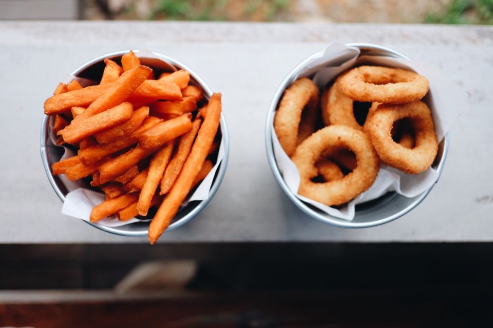 Sweet potato french fries and onion rings on a window sill