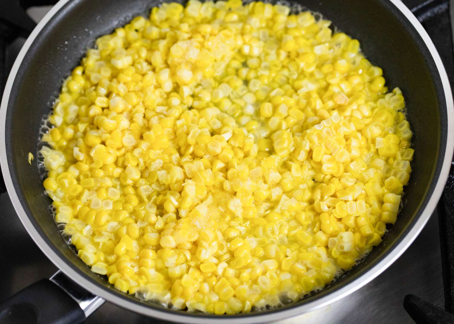 Corn kernels cooking in a saucepan with water and sugar