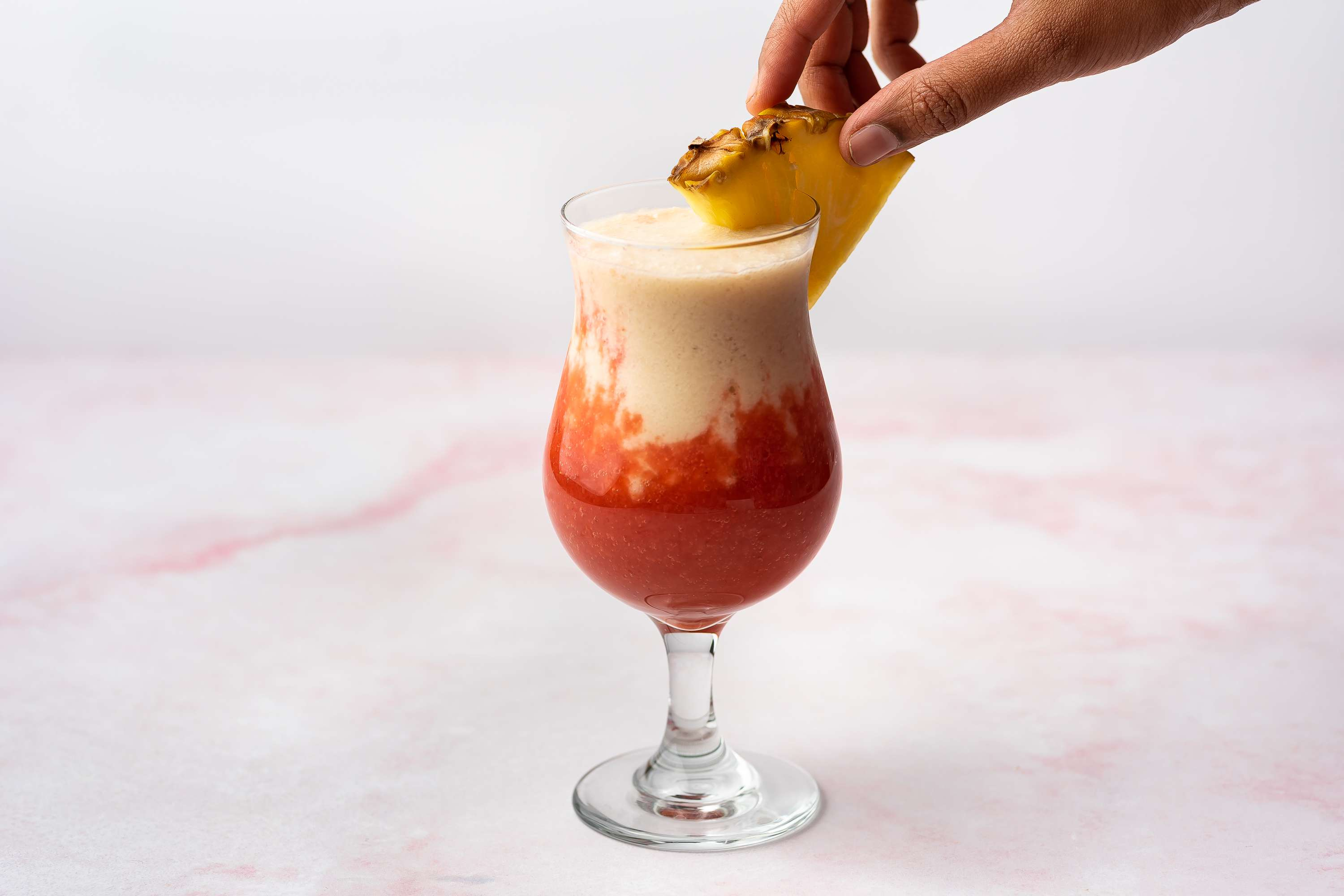 Lava Flow Hawaiian Tropical Drink in a glass garnished with pineapple
