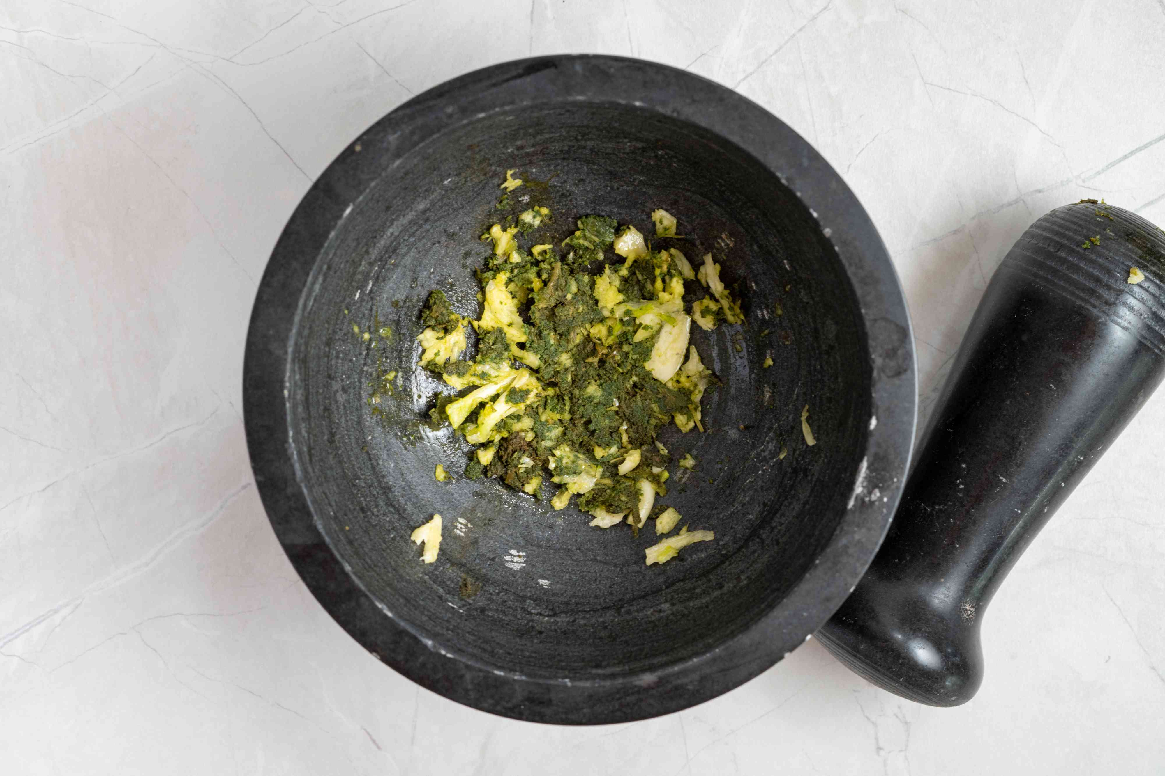 add garlic to the sage in the mortar and pestle