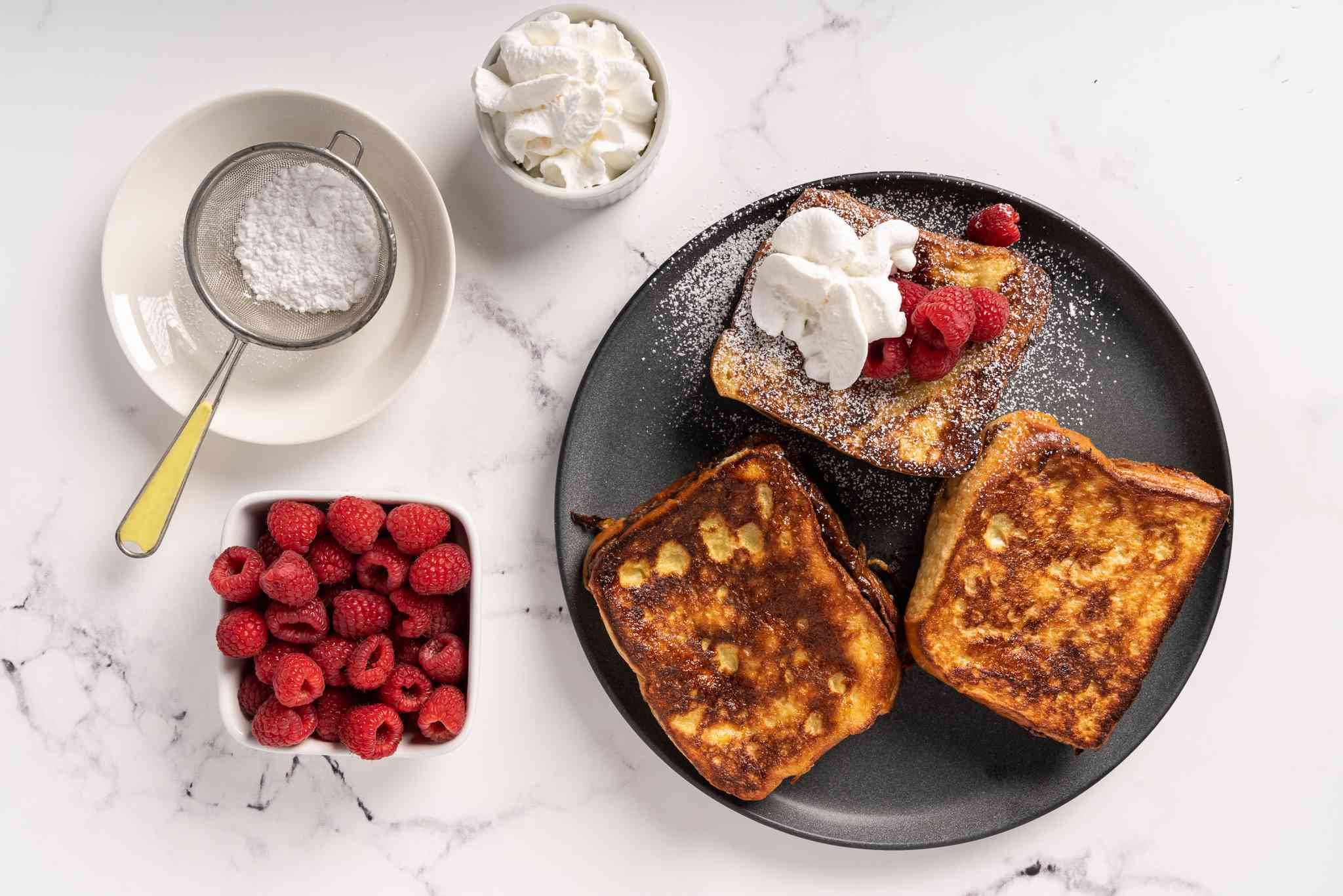Nutella French Toast on a plate topped with raspberries, whipped cream and powdered sugar