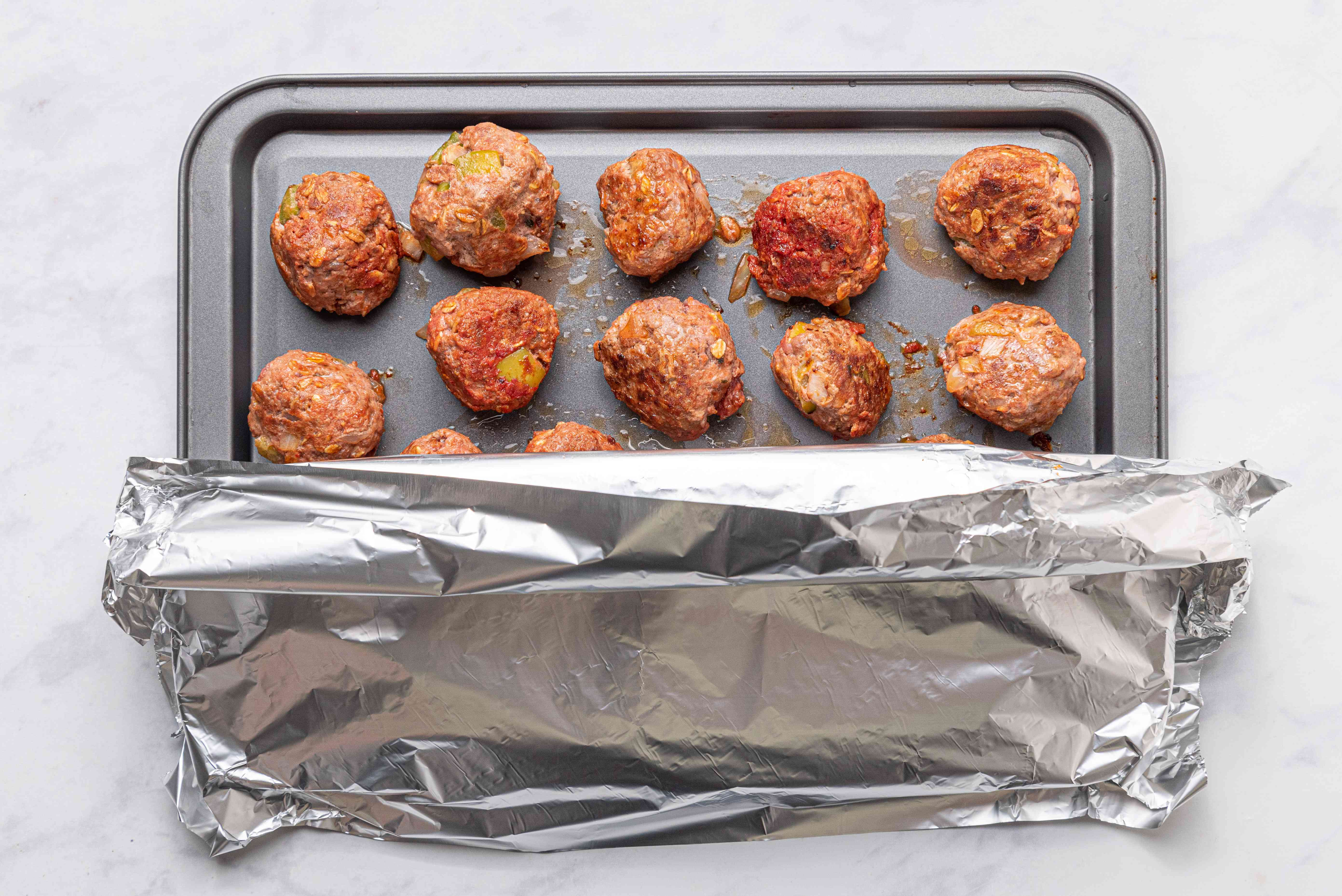 meatballs on a baking sheet, covered with aluminum foil