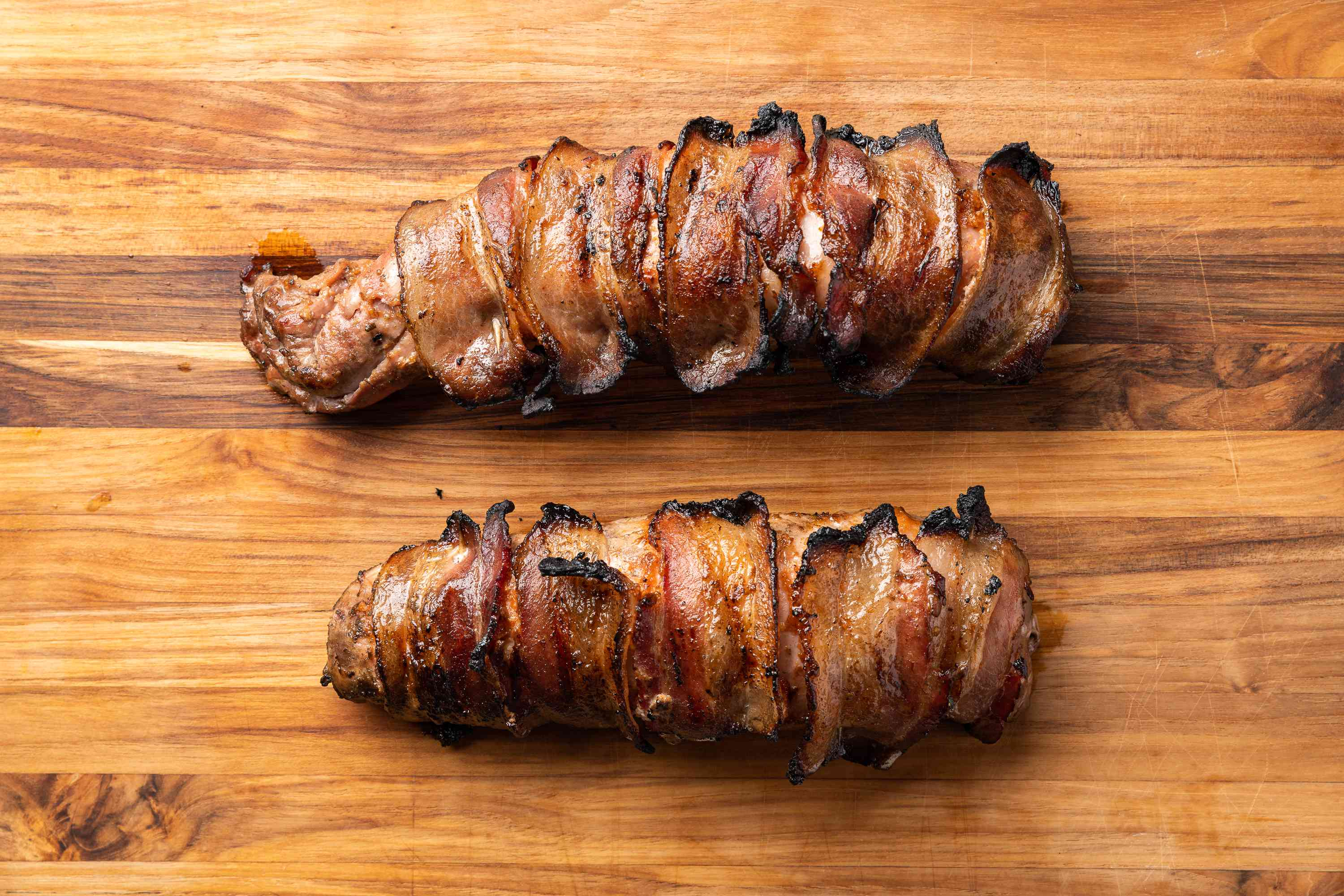 Grilled Bacon-Wrapped Pork Tenderloin on a wood surface