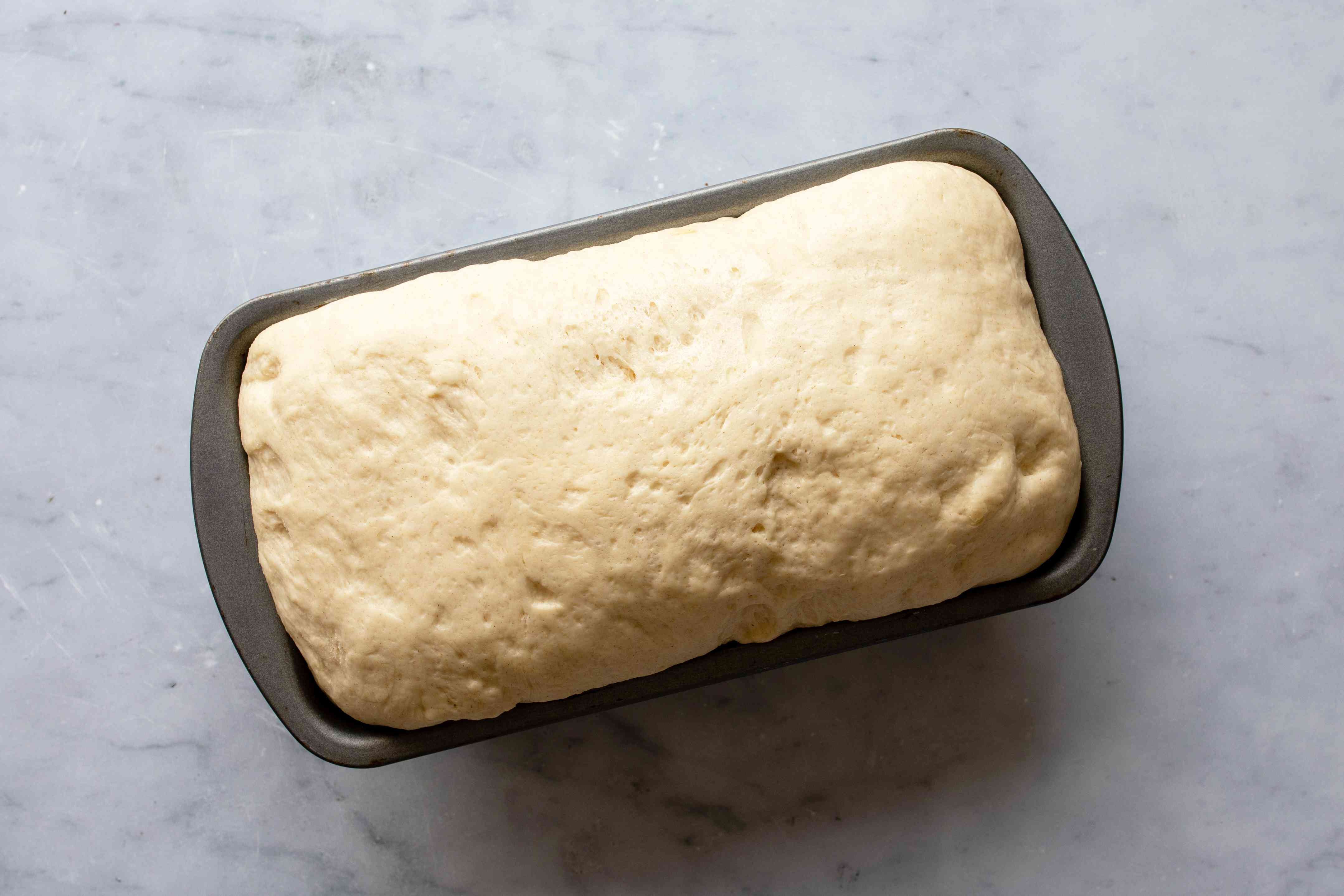The risen dough in a metal bread pan