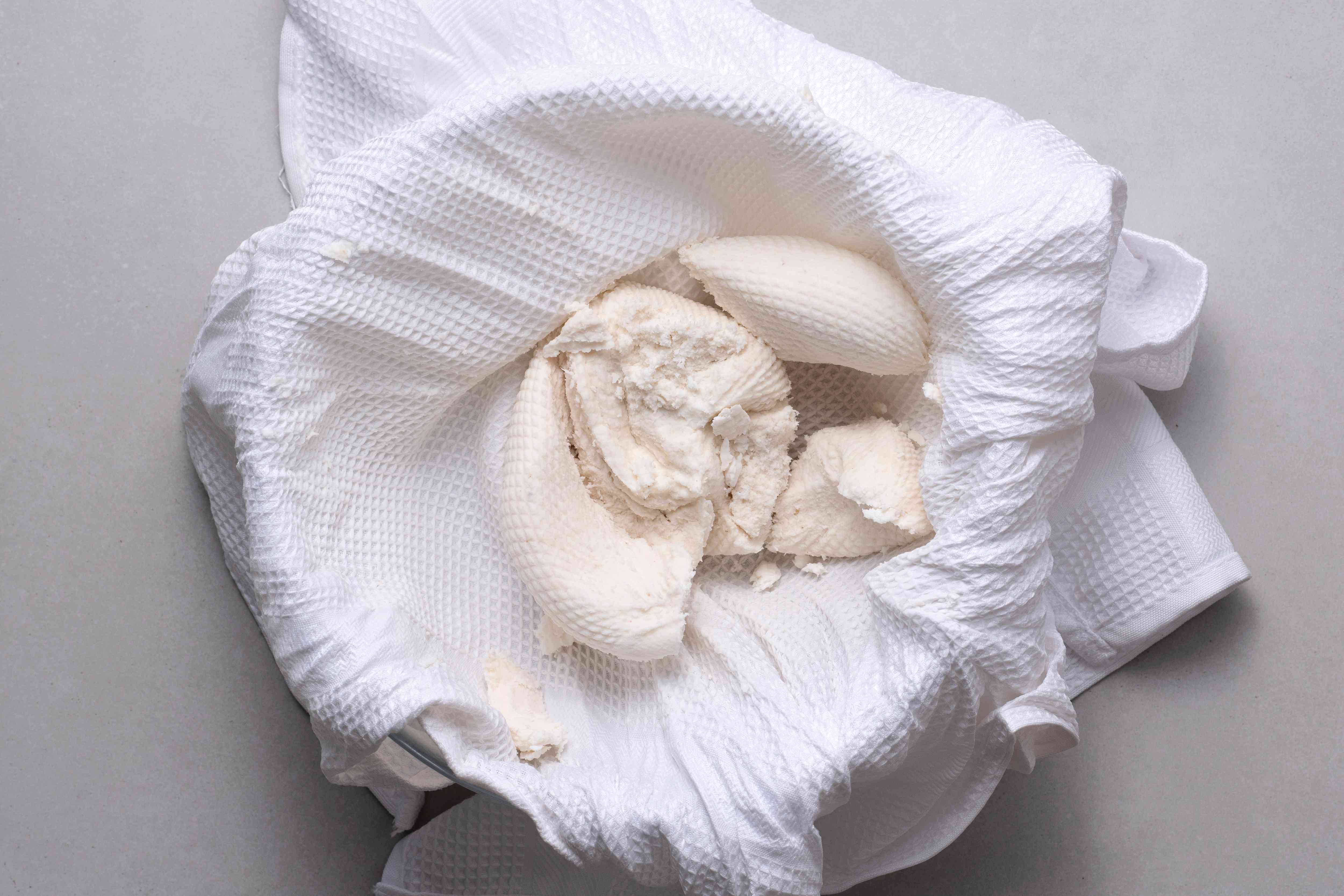 Using cheesecloth or a clean cotton towel, squeeze the grated cassava