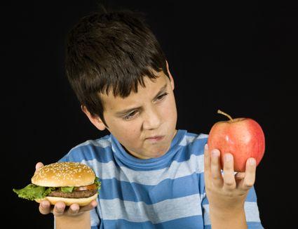 A child choosing between a hamburger and an apple