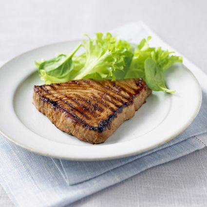 Marinated tuna steak served with lettuce on white plate and folded napkin