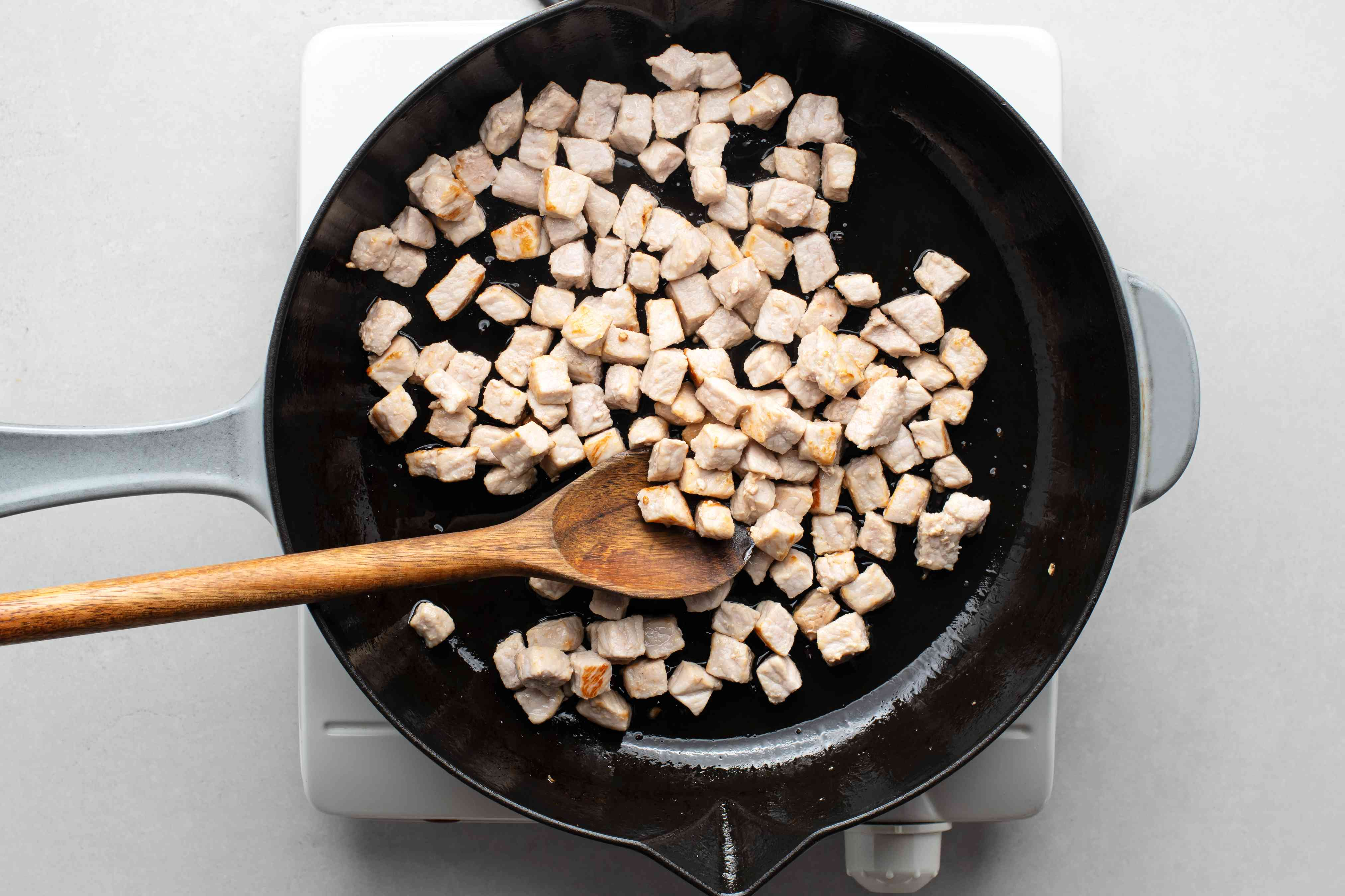 pork cooking in a skillet with oil