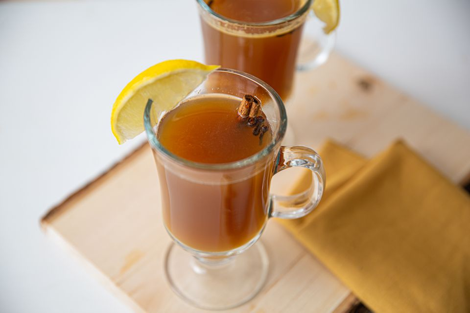 Hot apple toddy cocktail in a glass garnished with lemon and cinnamon