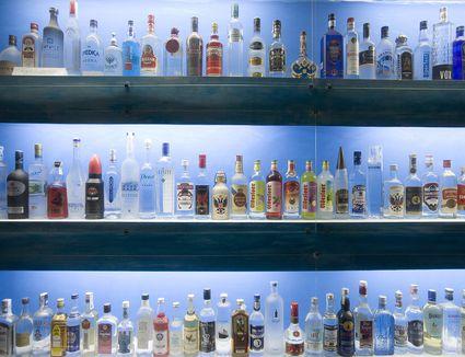 Dozens of bottles of vodka backlit and lined up on shelves