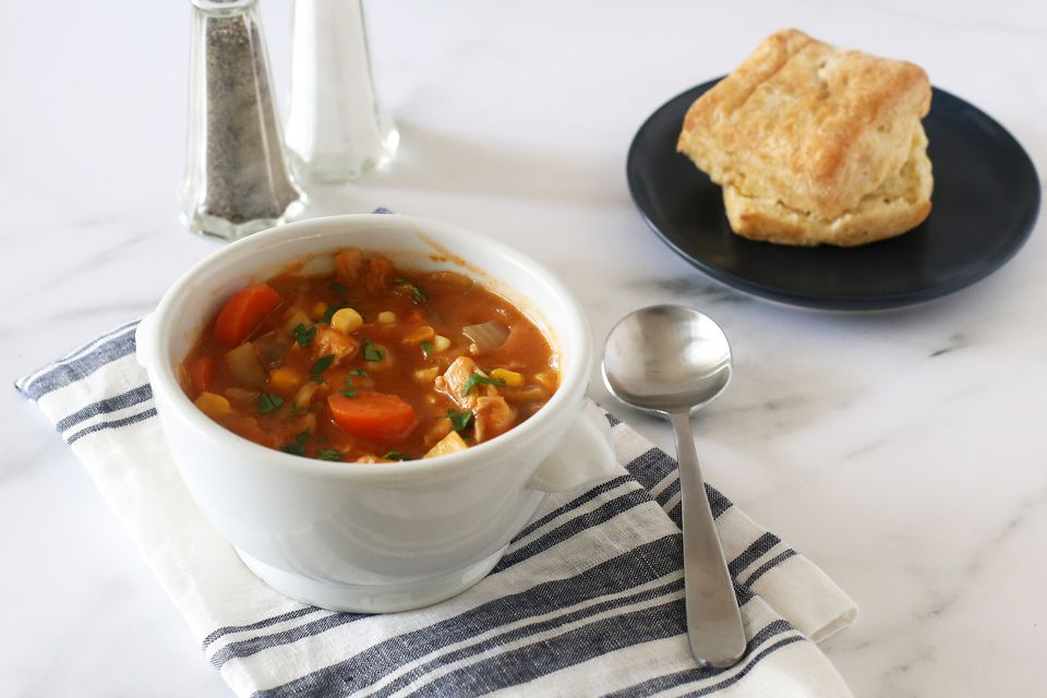 Chicken stew in a bowl with a biscuit.
