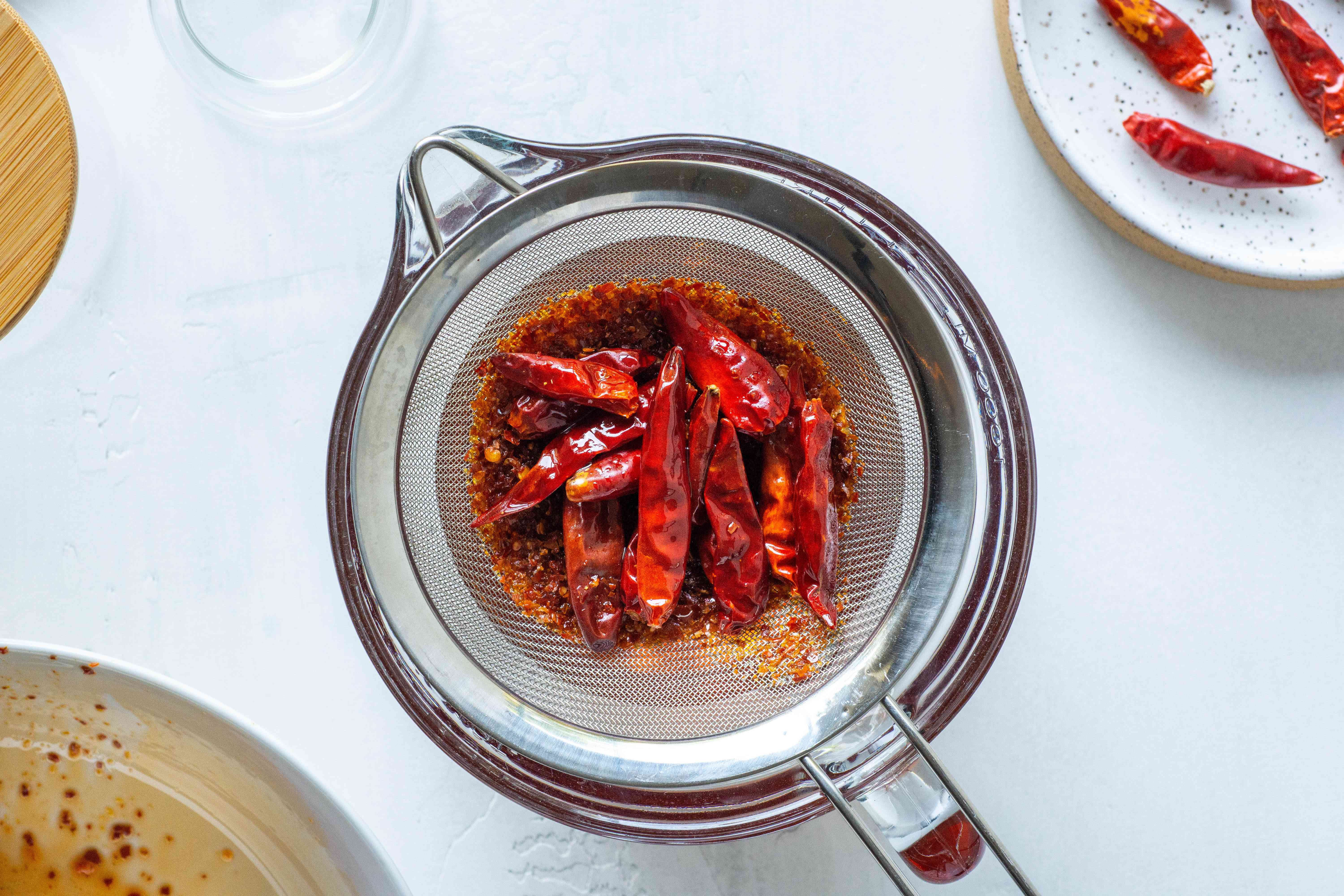 crushed and whole Chiles in a metal strainer