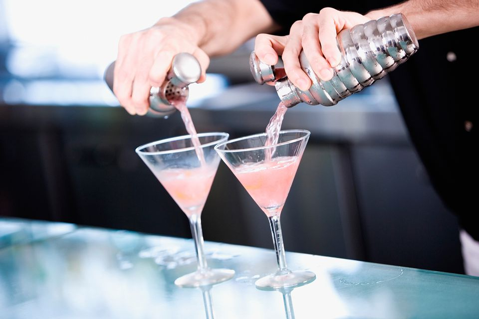 Bartender pouring pretty pink martinis