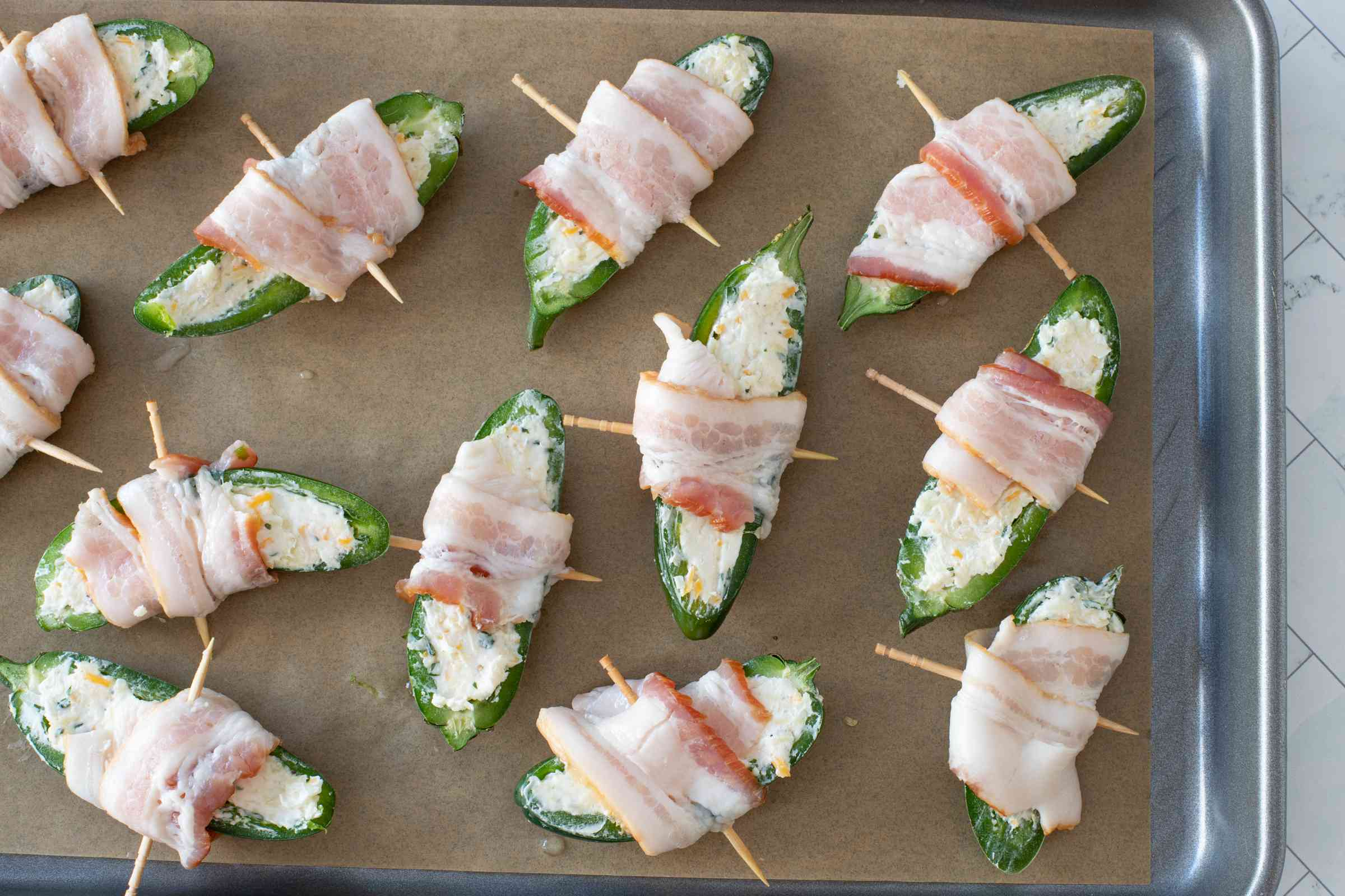 bacon-wrapped jalapeno poppers prep arranged on a baking pan