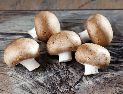 Cremini mushrooms on a wooden background