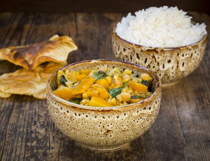 A bowl of pumpkin curry with rice and chapatis