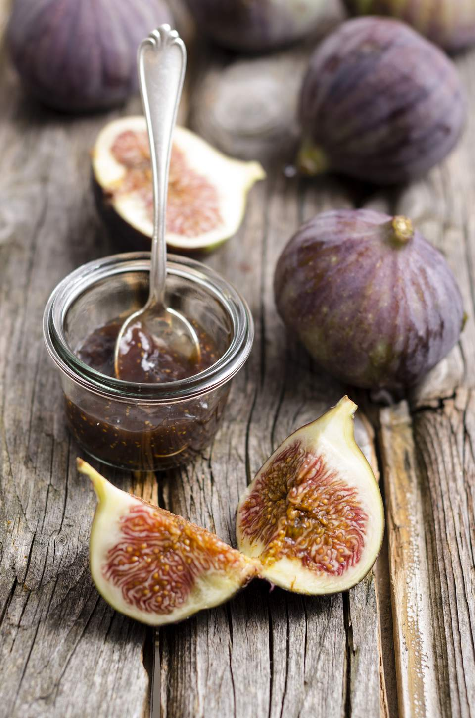 Figs and a glass of fig jam on a wooden table
