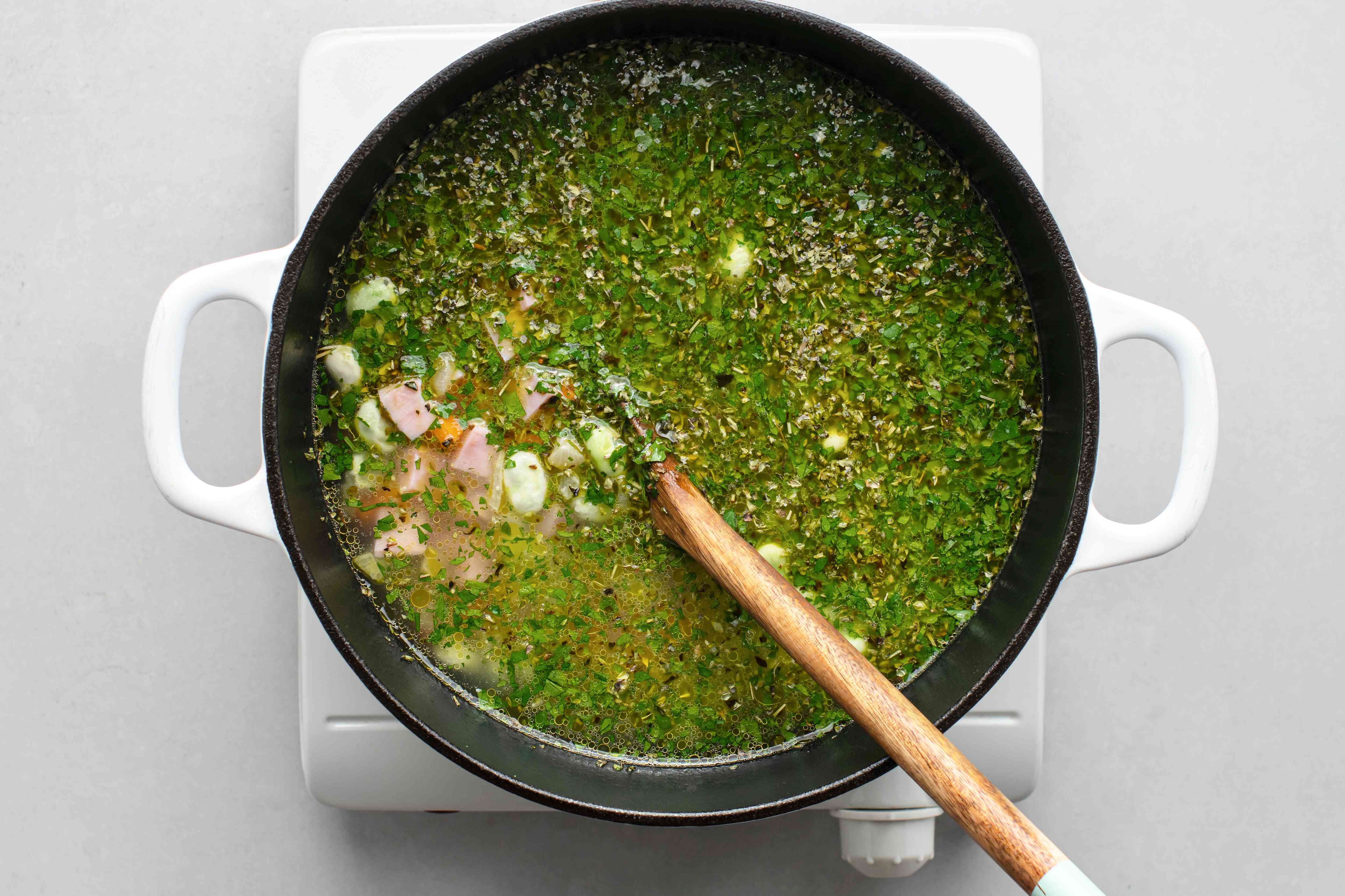 Add the ham, frozen lima beans, parsley, and marjoram to the vegetable mixture in the Dutch oven