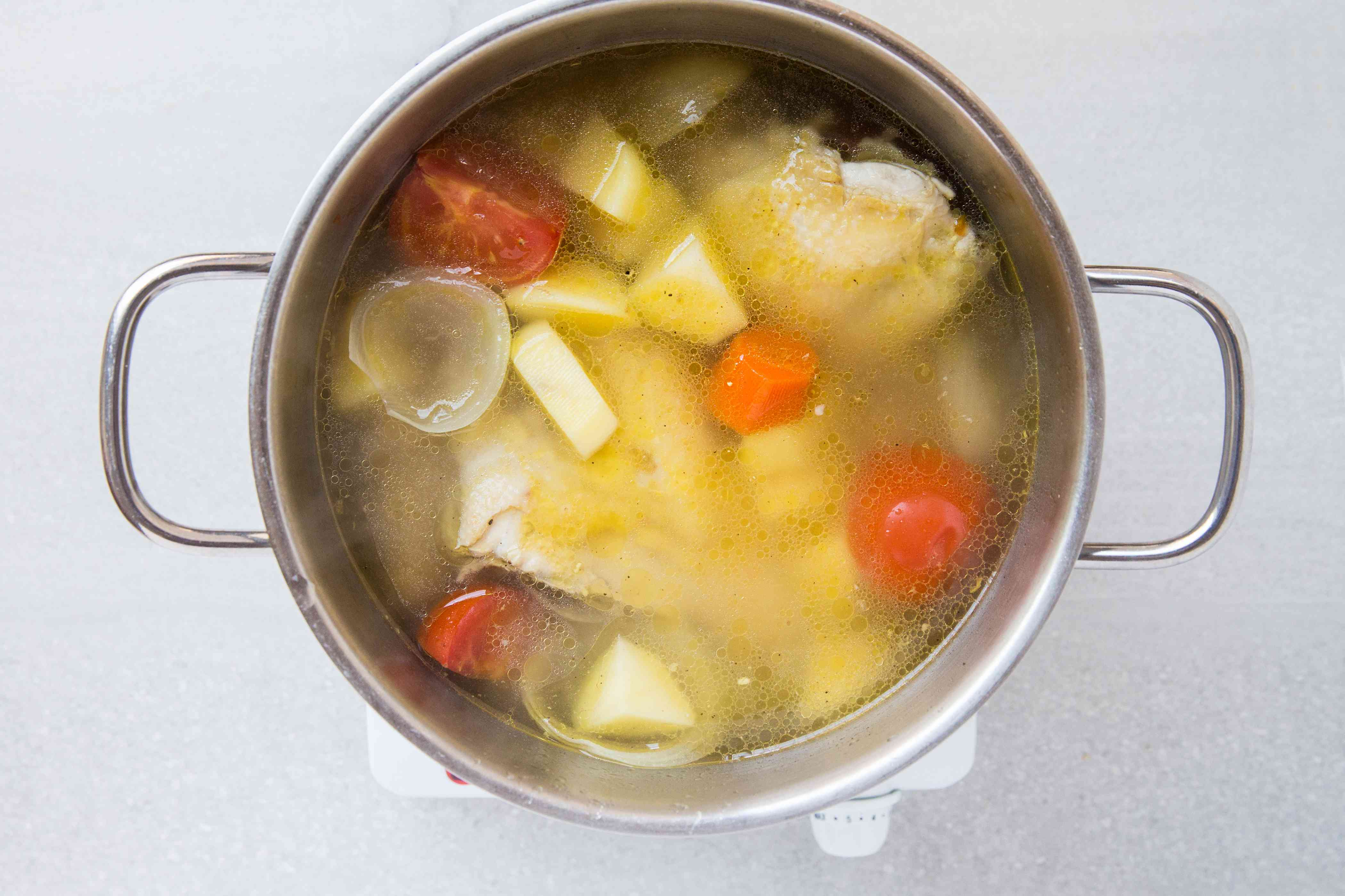 Potatoes are added to the pot with the chicken and vegetables