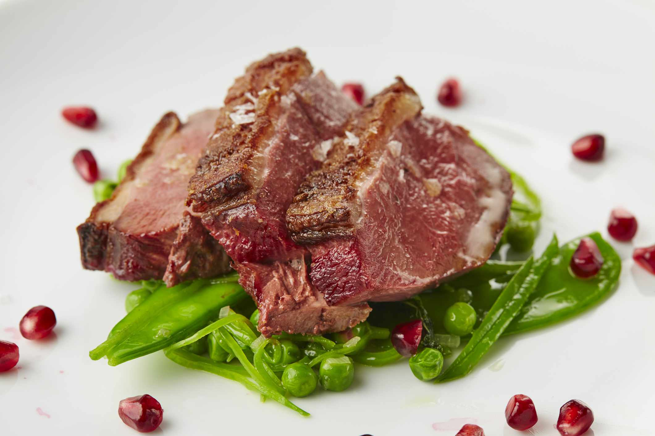 Plate of grilled duck on spring peas with pomegranate seeds