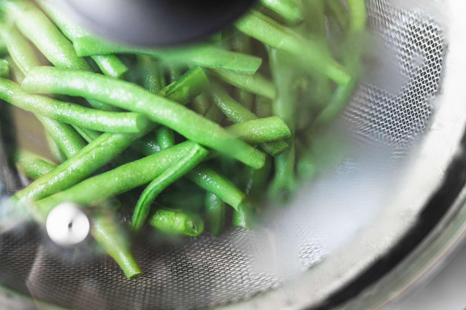 steaming green beans in strainer