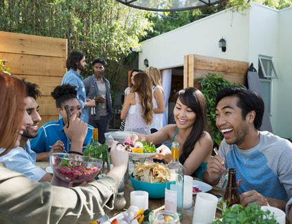 Friends laughing eating drinking at patio table
