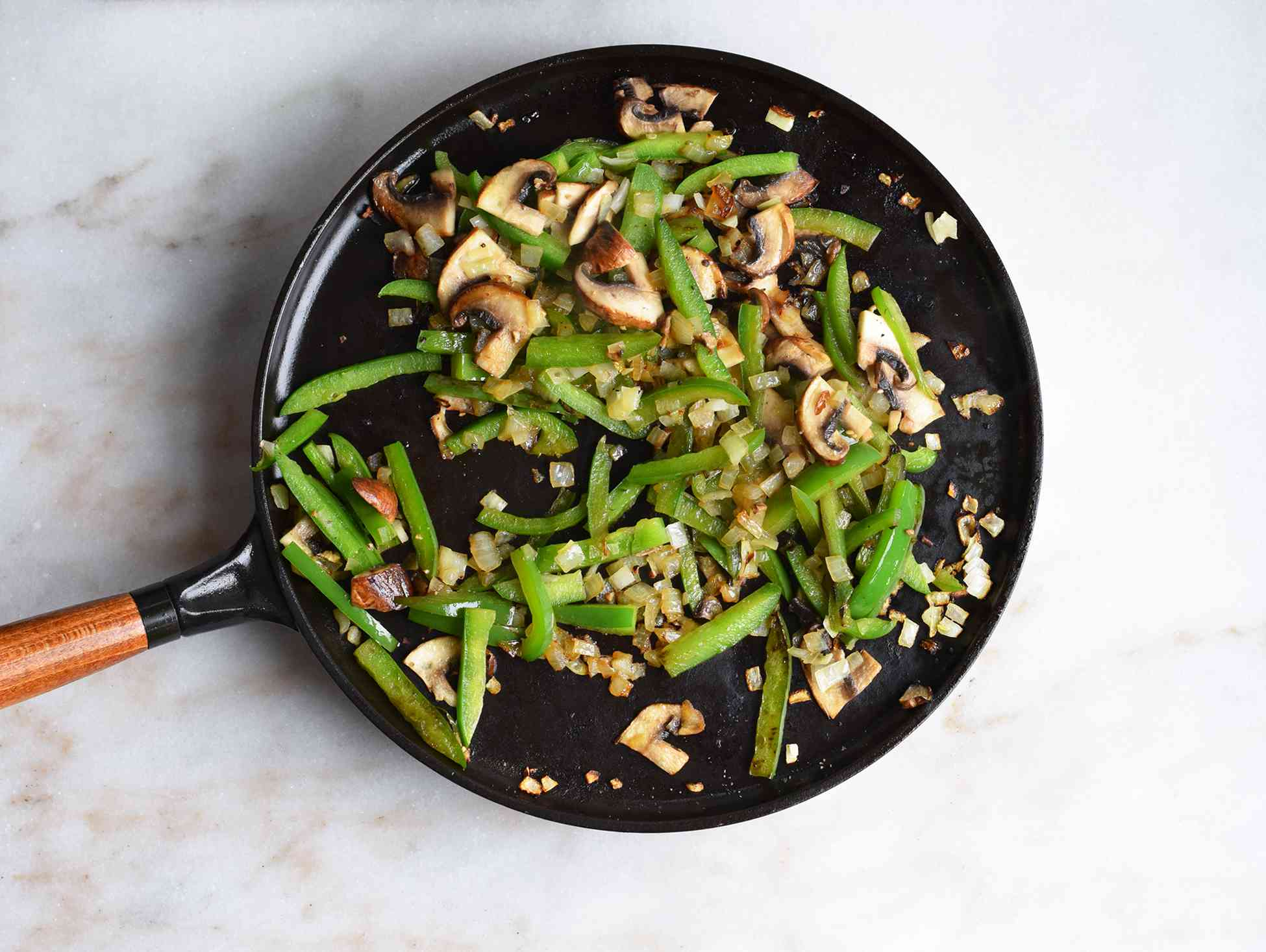 peppers, mushrooms, and onions sauteed in a pan