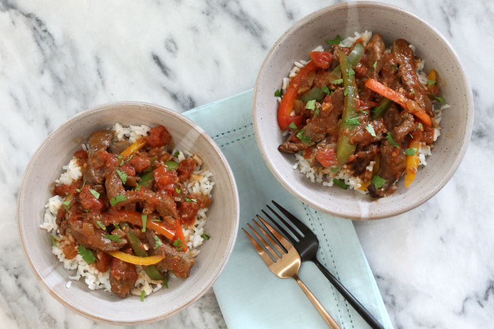 Crock pot pepper steak in bowls with rice.