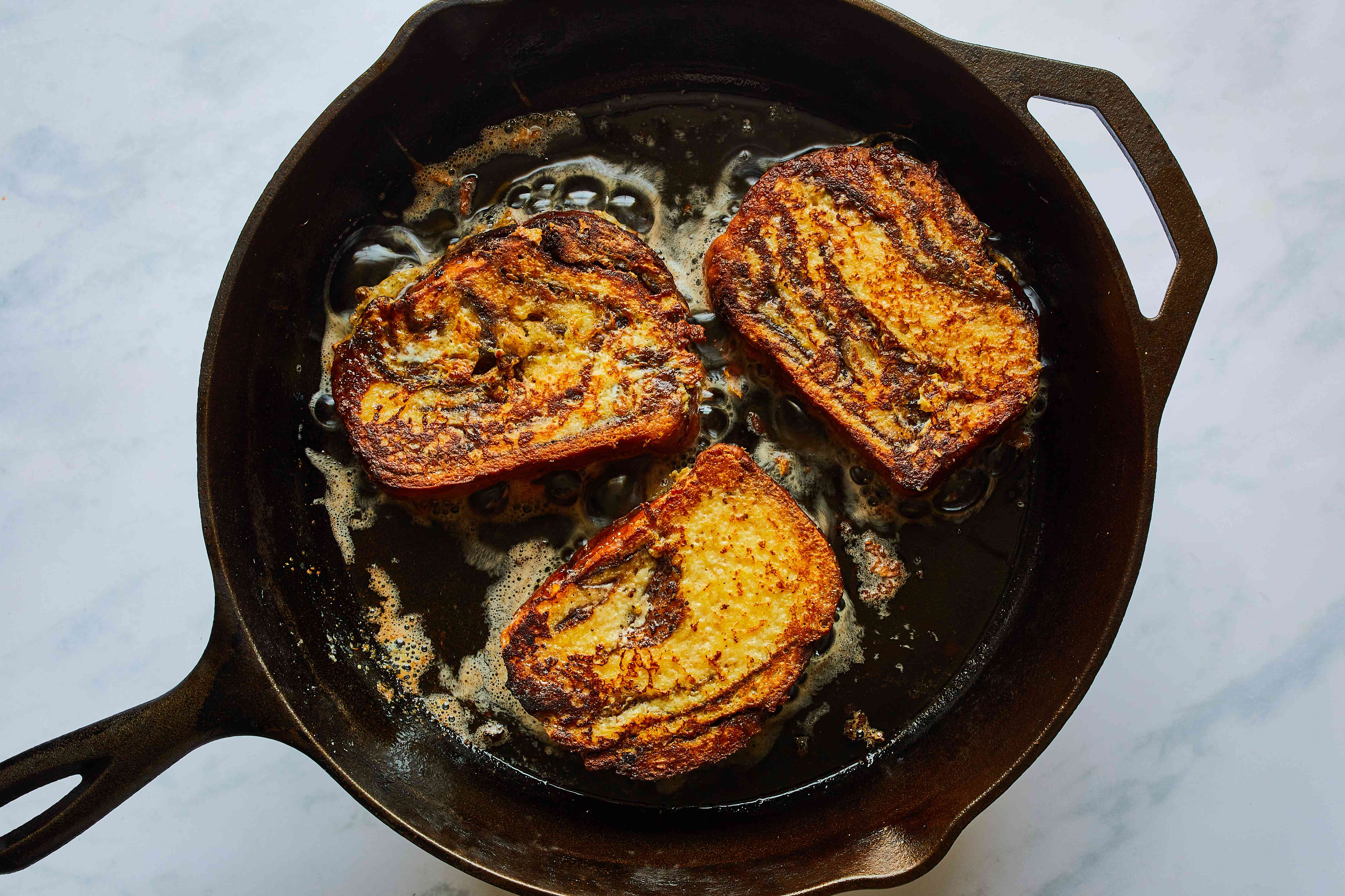 babka french toast slices cooking in butter in cast iron pan