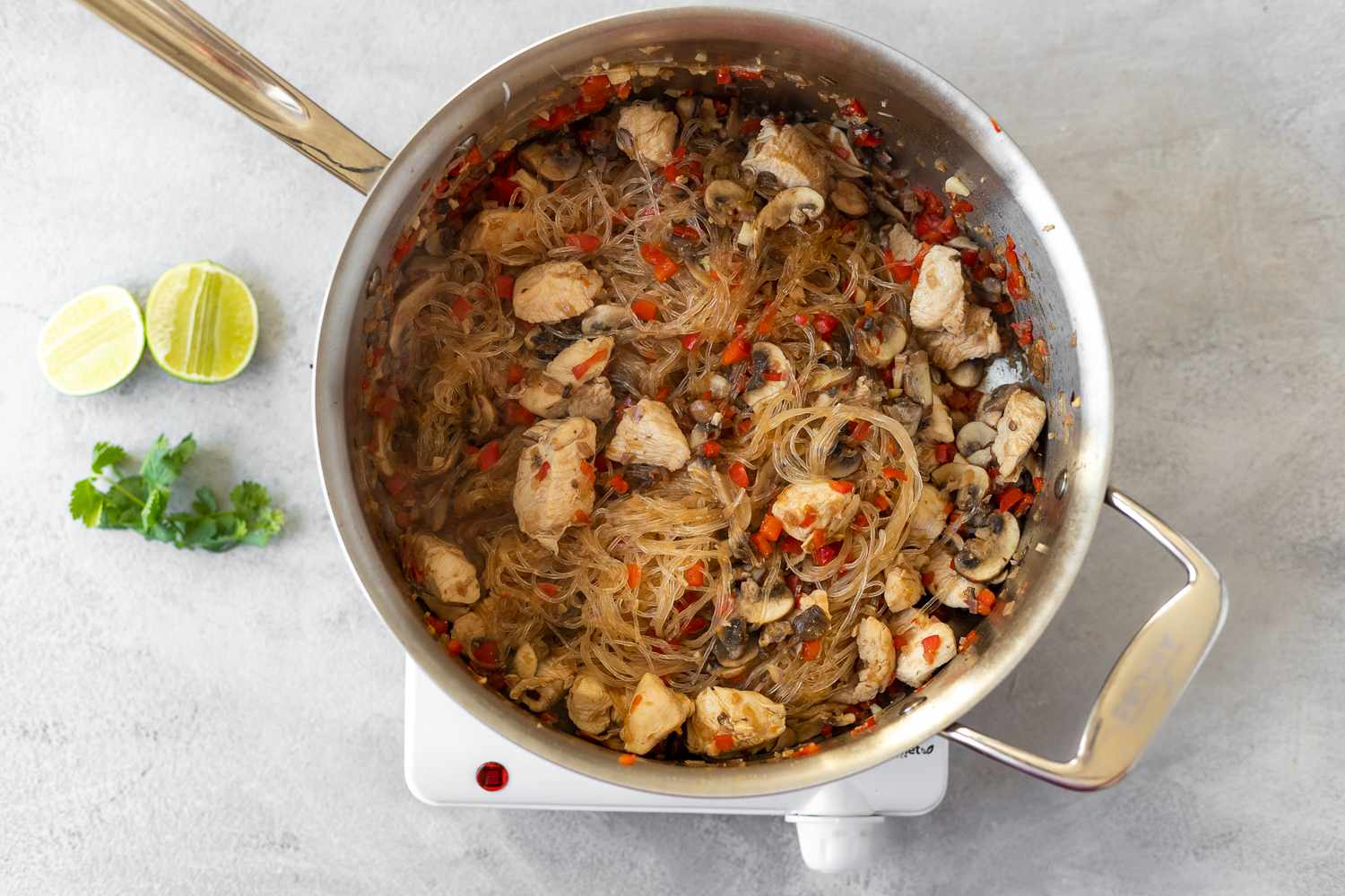 add the glass noodles to the chicken and vegetables in the skillet