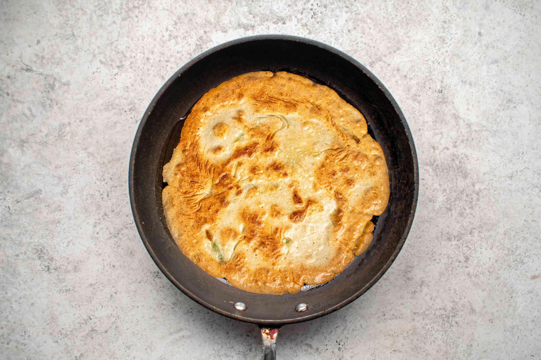 Pa jun (Korean scallion pancake) cooked on one side in a pan