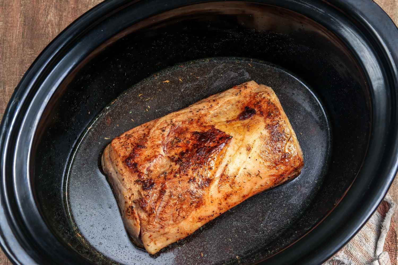 Pour liquids over pork in slow cooker