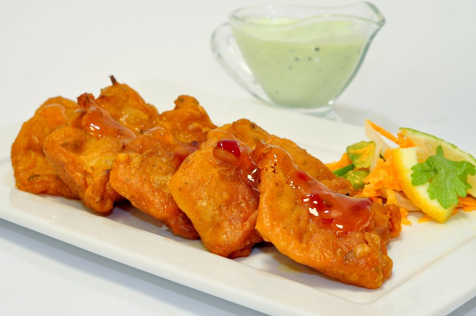 Fish Pakora on a white plate with garnish