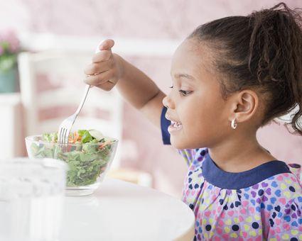 Young girl eating salad