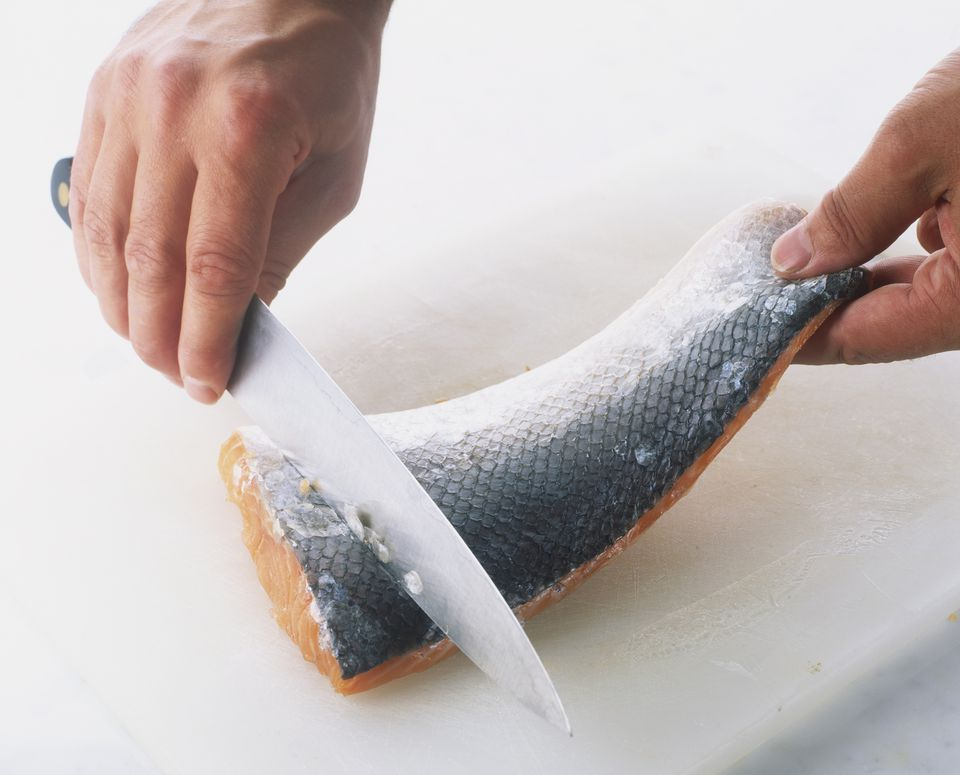 Person descaling fish with knife