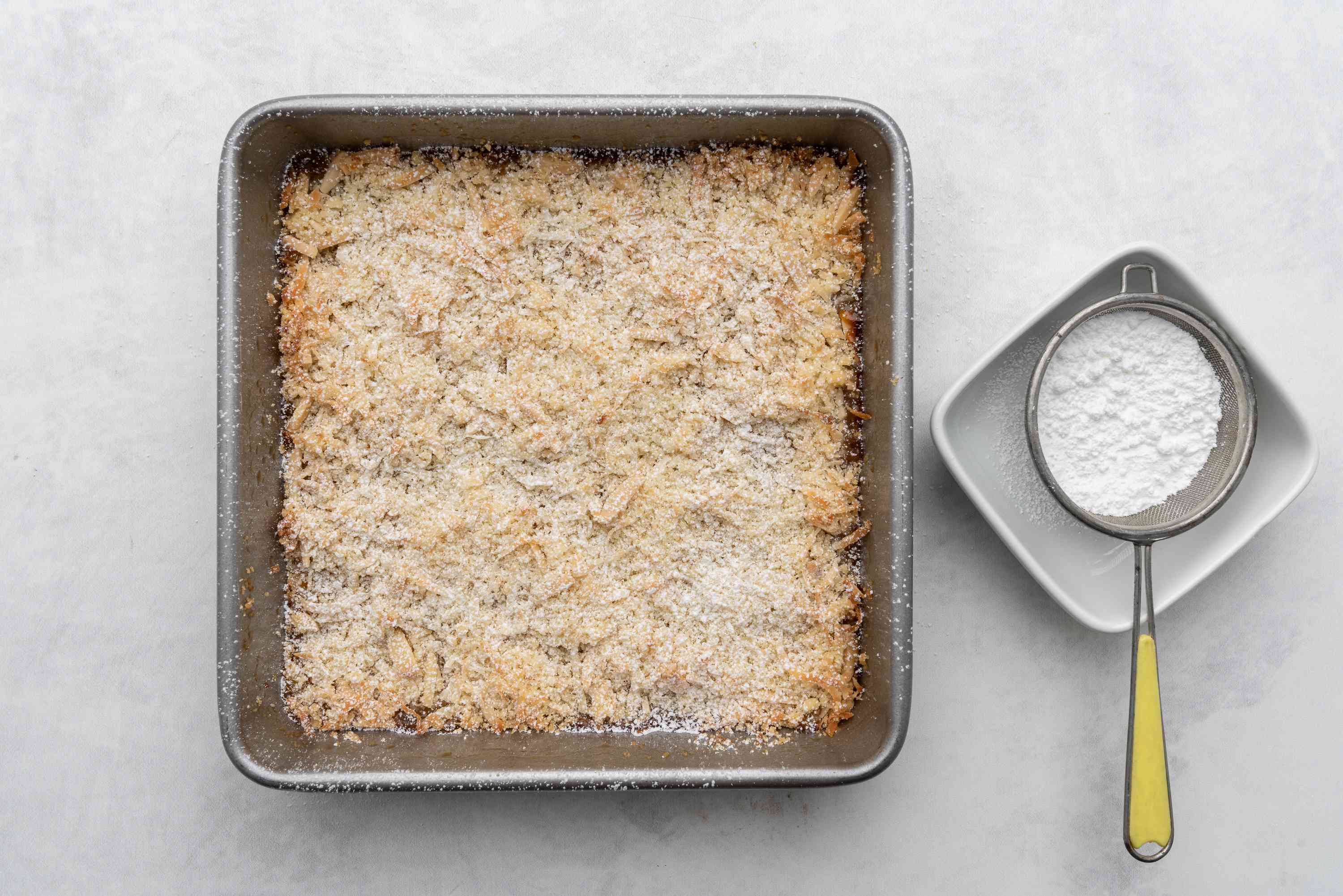 powdered sugar being sifted on top of bars