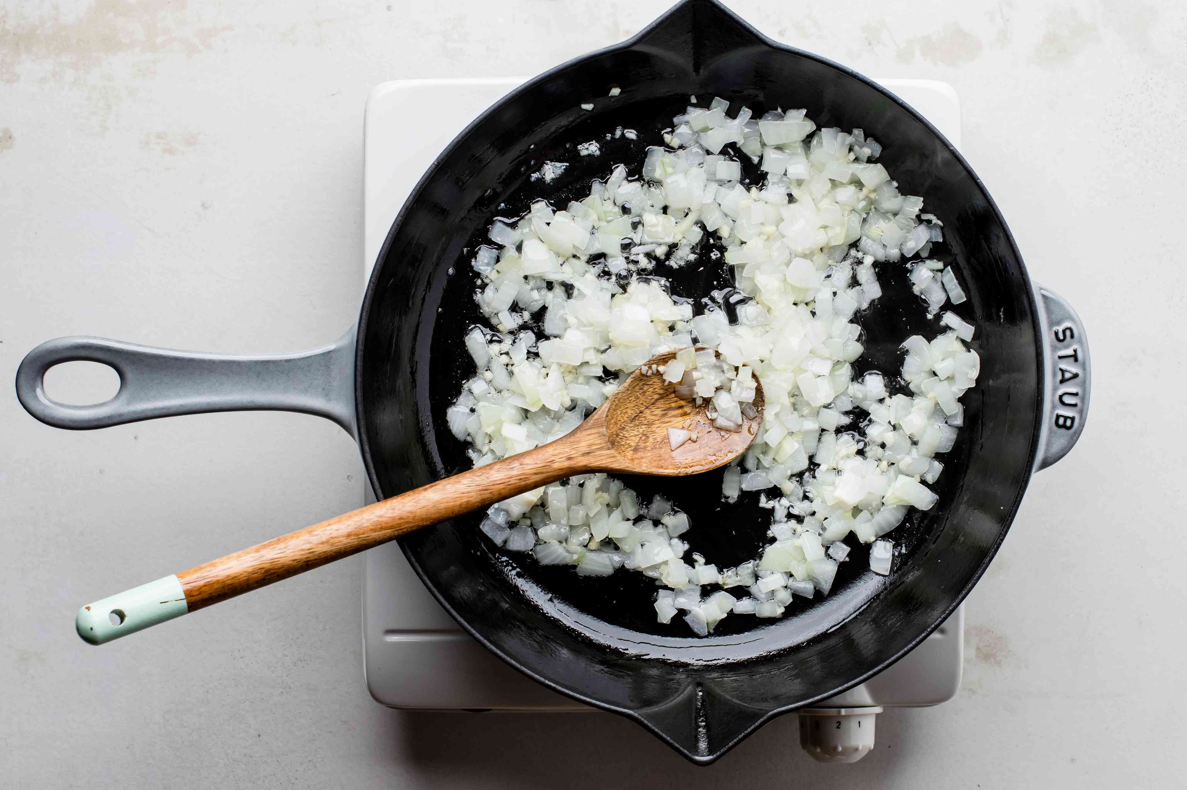 Onion and garlic are sautéed in a skillet, stirred with a wooden spoon