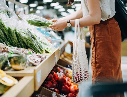 Woman shopping for fresh organic groceries in supermarket