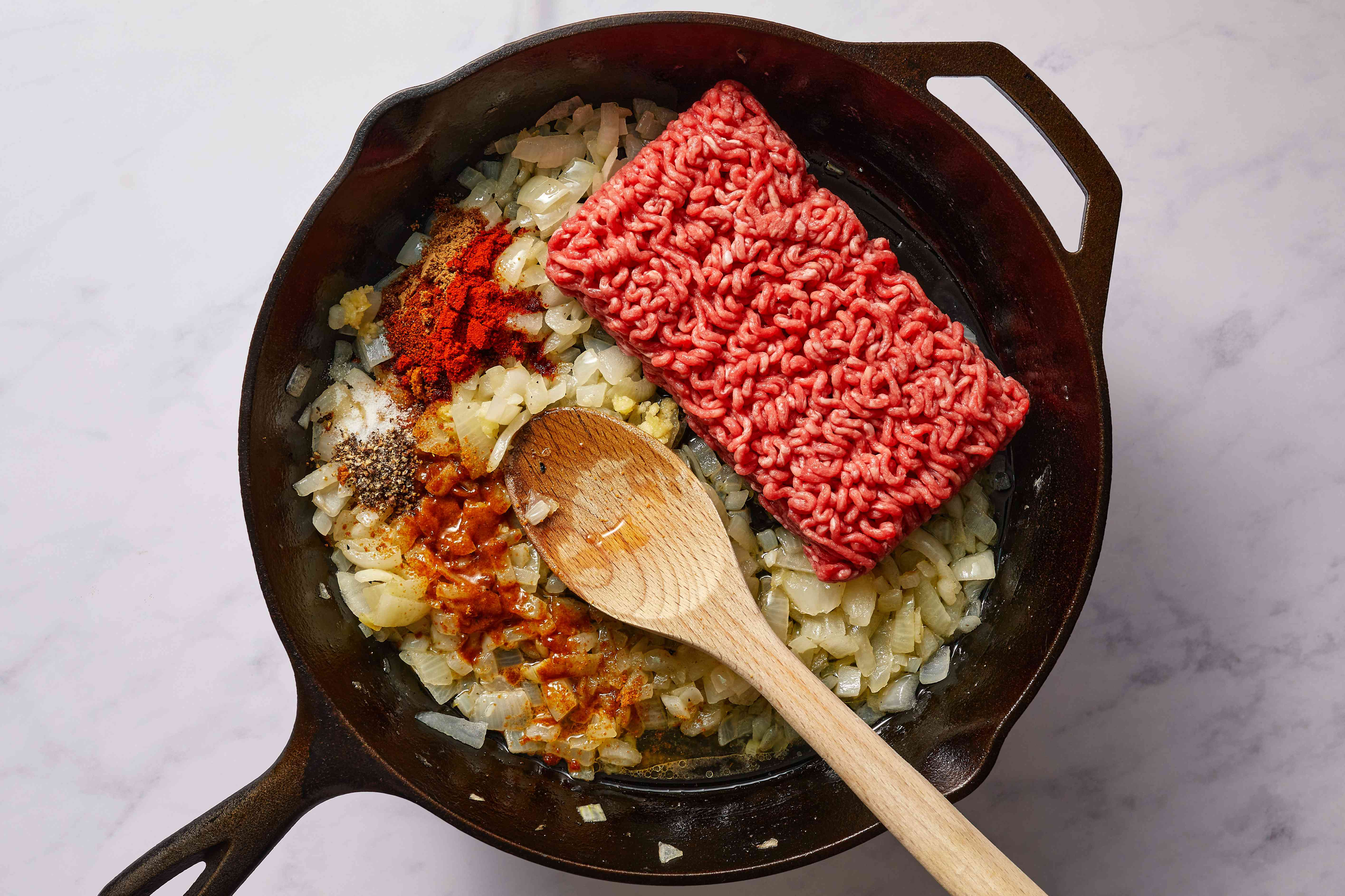 ground meat and spices added to the onions in the skillet
