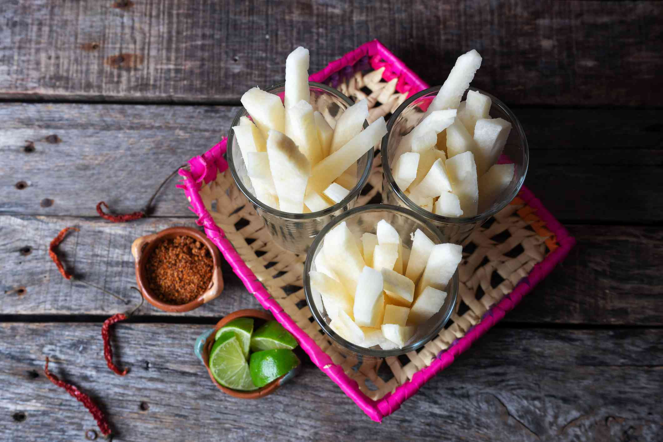 Jicama sliced in small bowls on a colorful basket