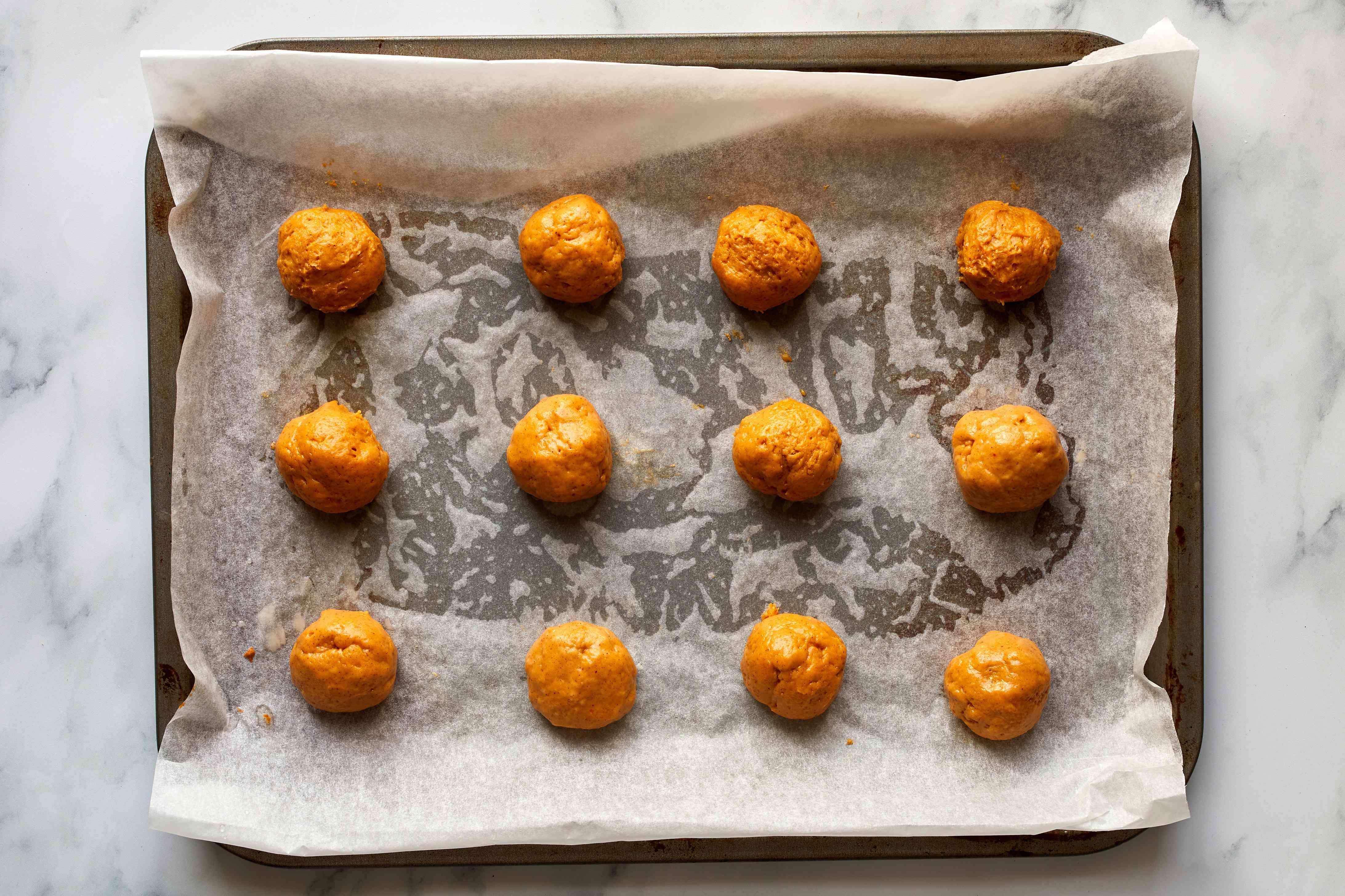 pumpkin cookie dough balls on a baking sheet