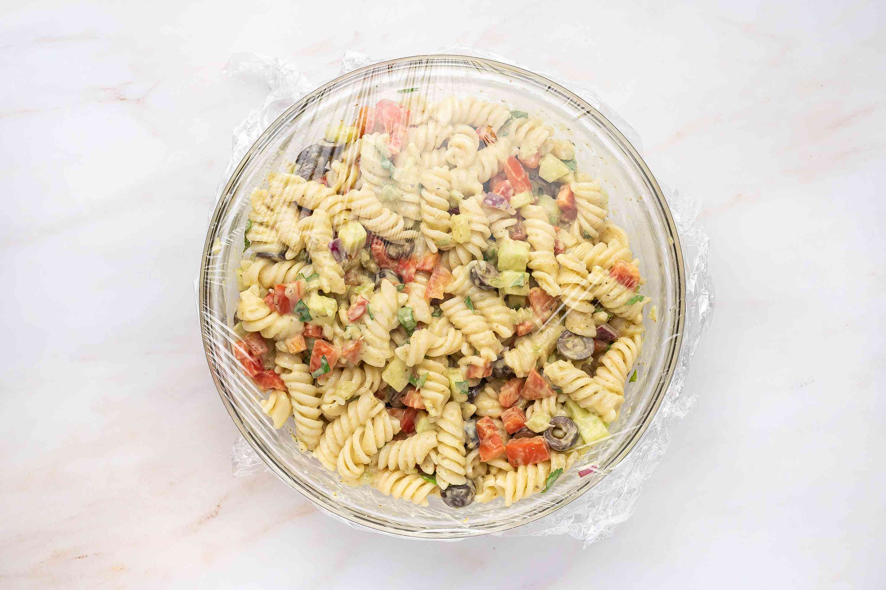 Garden Pesto Pasta Salad With Rotini in a bowl, covered with plastic wrap