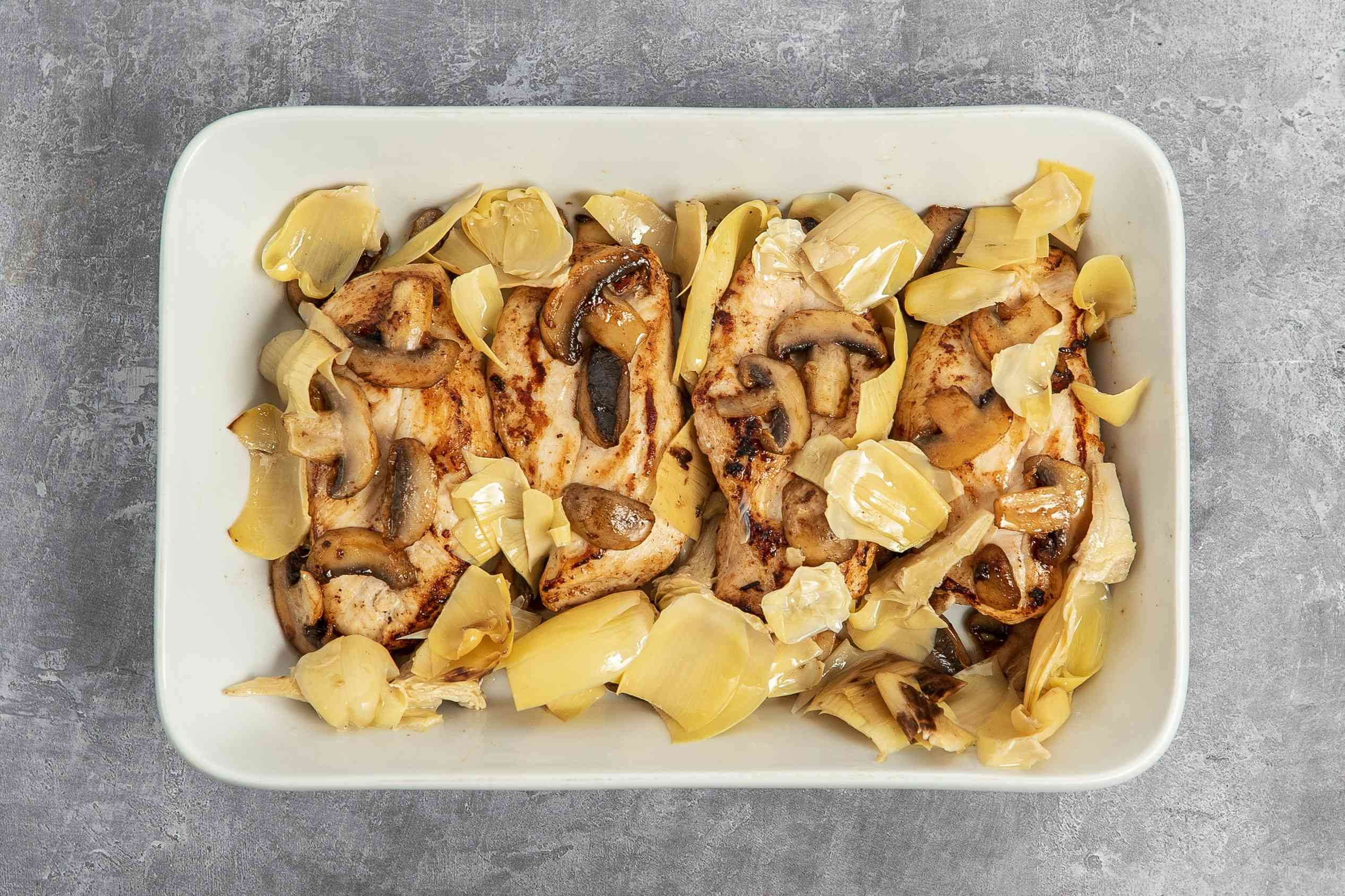 chicken, mushrooms and artichokes in a baking dish
