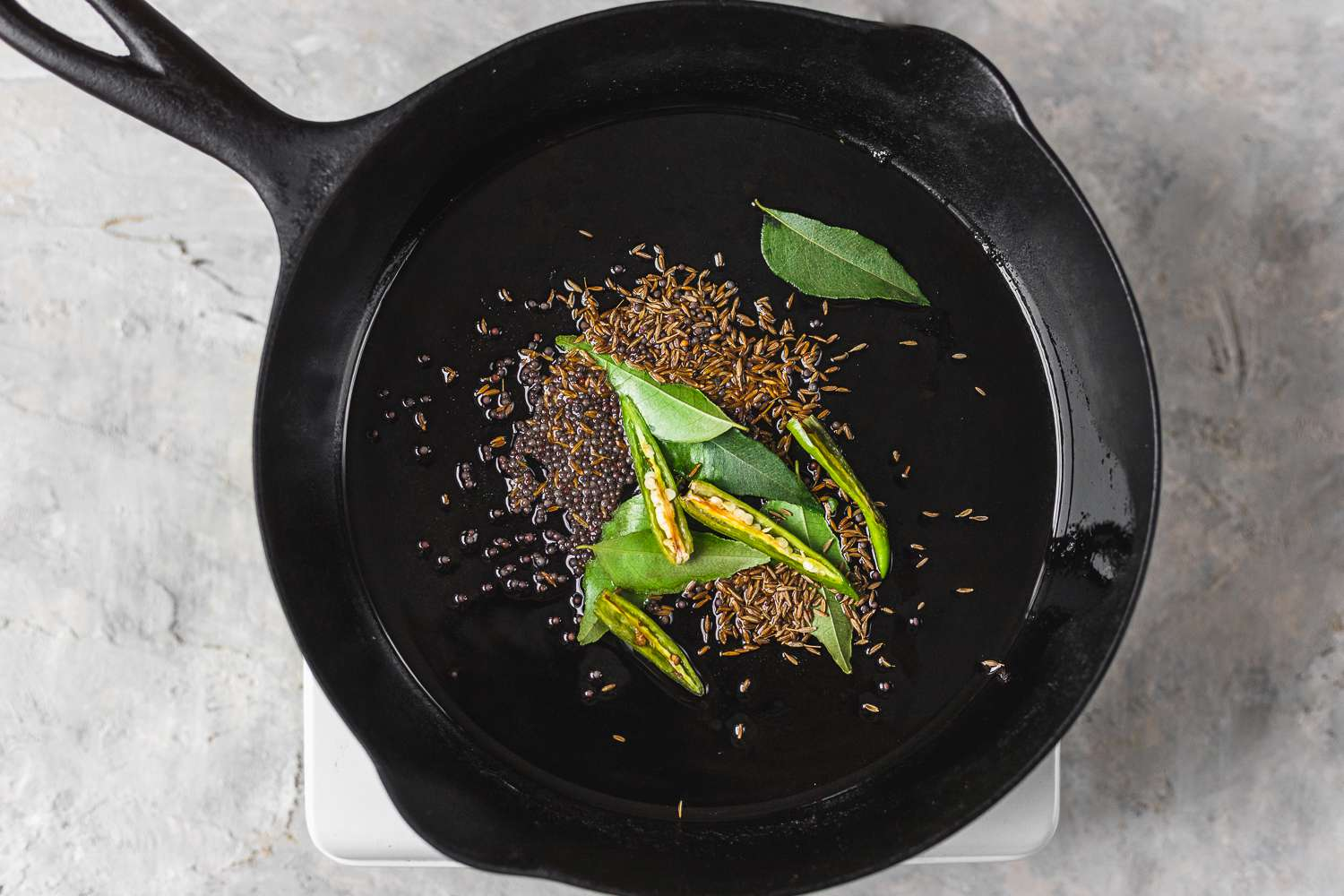 add curry leaves, cumin and mustard seeds, and green chilies to the oil in the pan