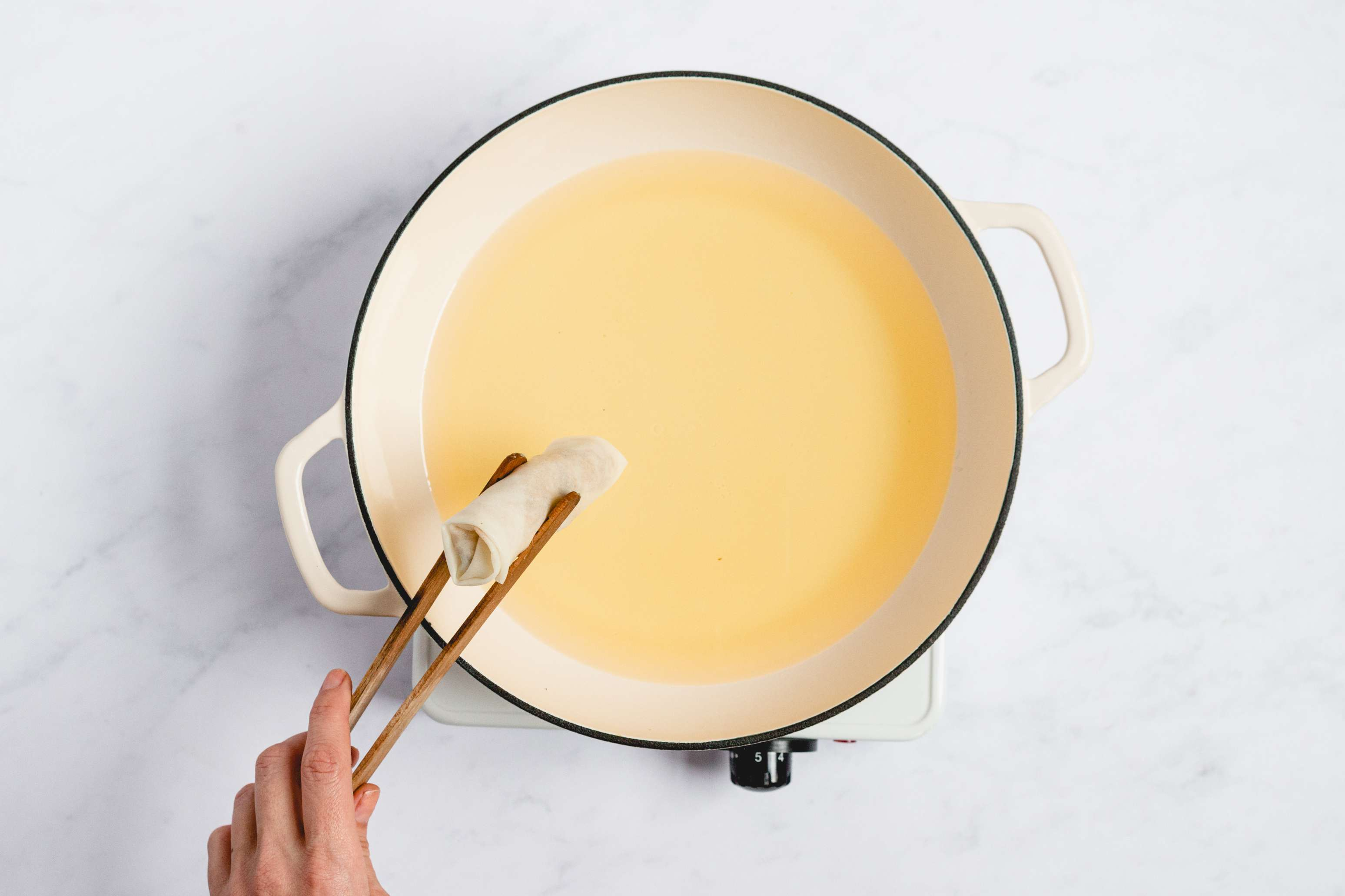 pot with oil, egg roll being held with tongs