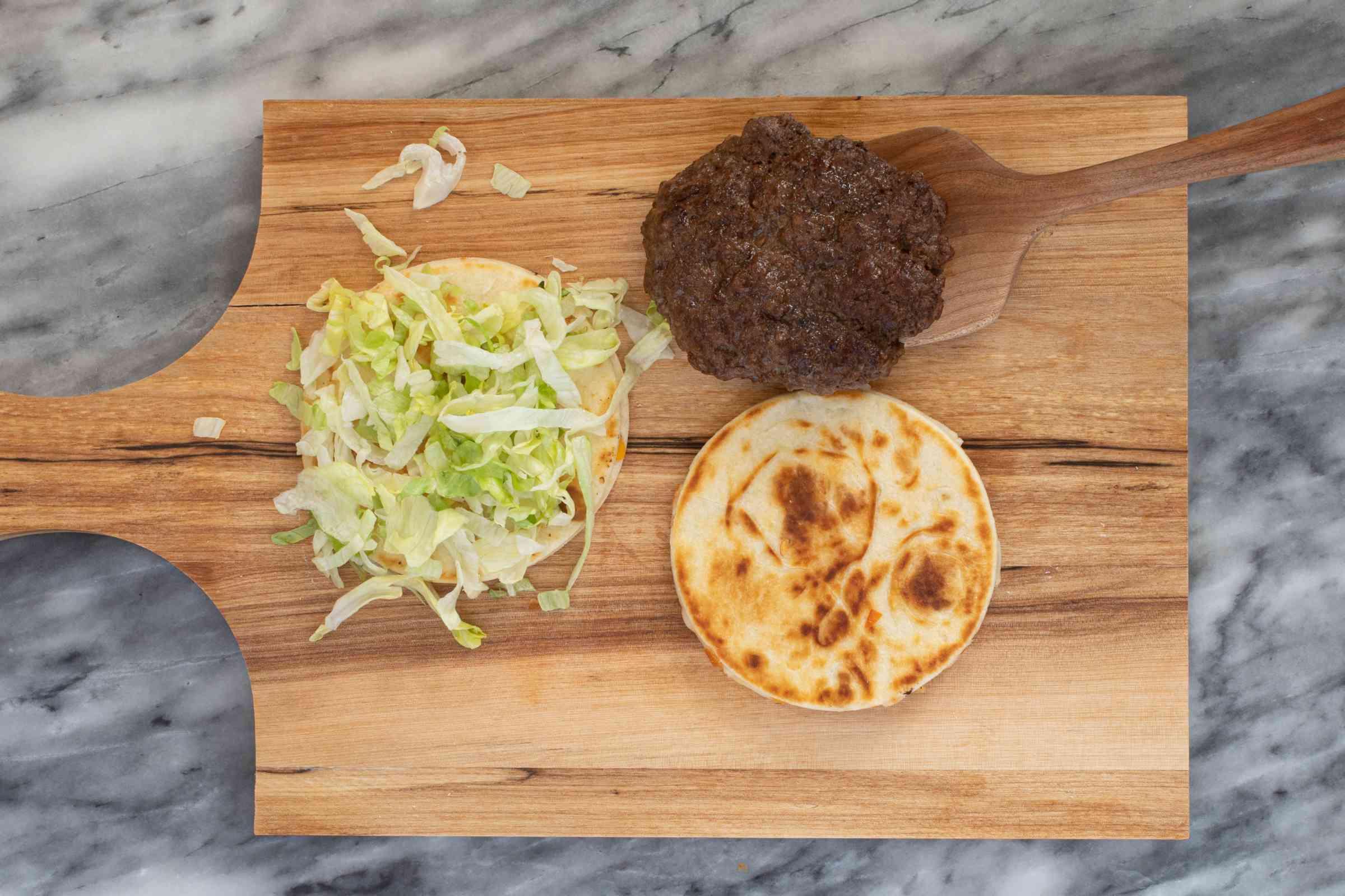 Assembling a quesadilla burger.
