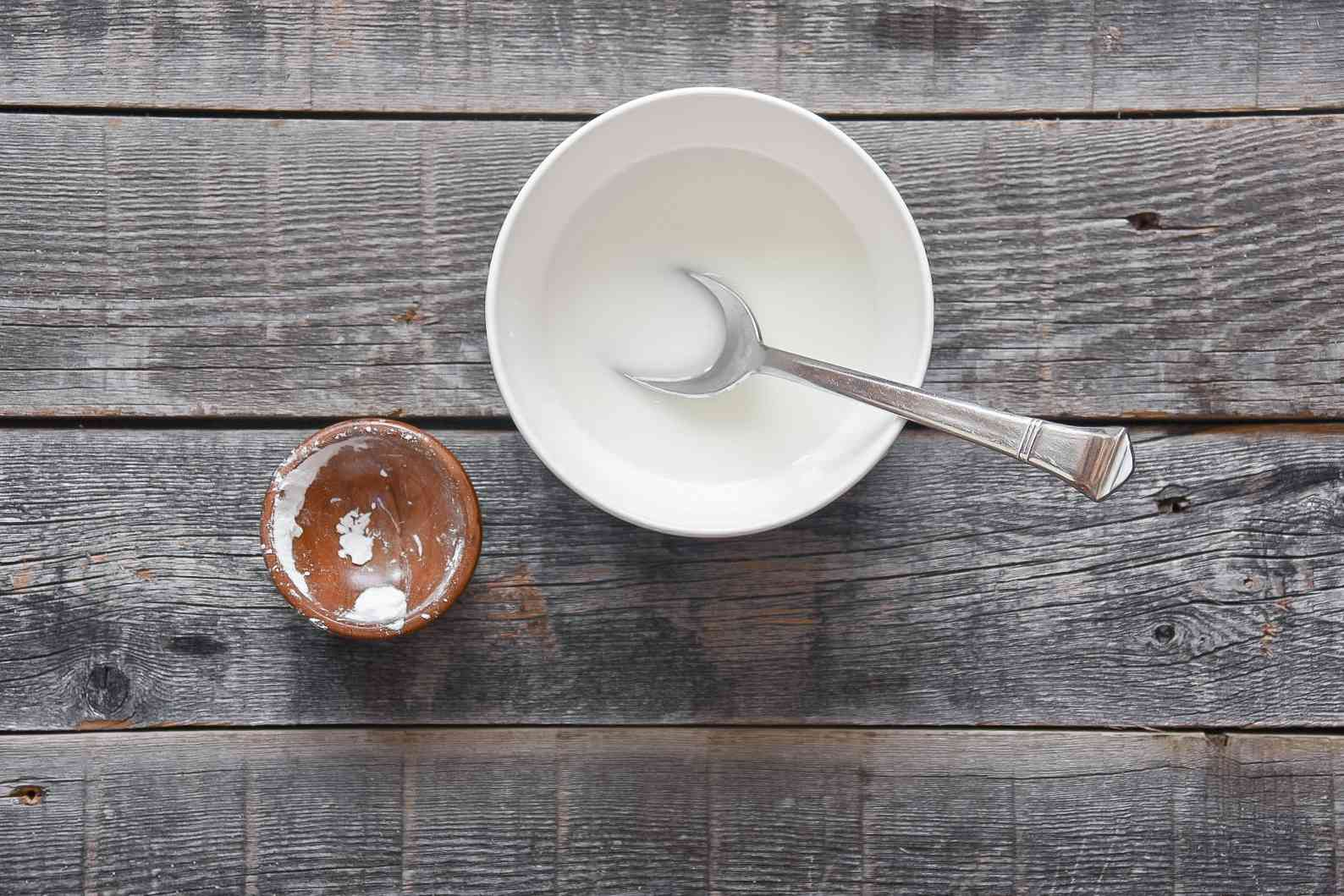 Cornstarch and water in a small white bowl, stirred with a metal spoon