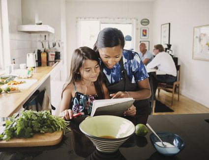 mom and daughter reading recipe book