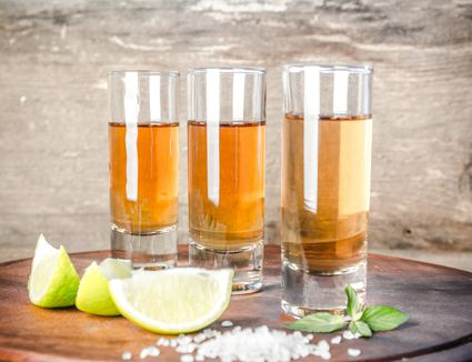 Glasses of tequila on the wooden board - stock photo