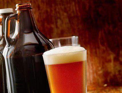 A full pint beside growlers of fresh beer.